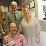 Seated: Larry Hertz.  Standing: Co-hosts Jonah Triebwasser, Sarah O'Connell